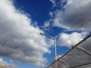 clouds and metal fence