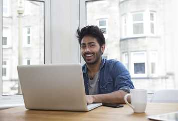 Asian man at home working on laptop.