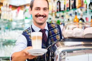 Barista im Cafe bietet Latte Macchiato im Glas an