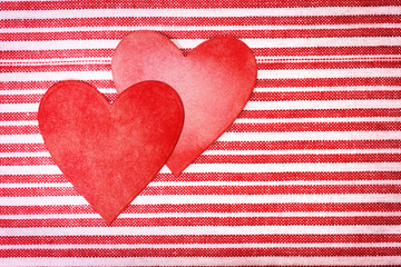 Two handcrafted paper hearts on striped background
