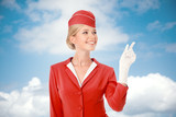 Charming Stewardess Dressed In Red Uniform Pointing The Finger.