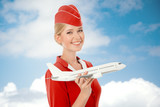 Charming Stewardess Holding Airplane In Hand. Sky With Clouds Ba