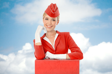 Charming Stewardess Dressed In Red Uniform And Suitcase. Sky Wit