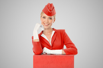 Charming Stewardess Dressed In Red Uniform And Suitcase On Gray
