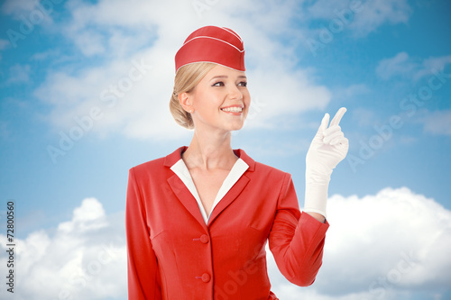 Charming Stewardess Dressed In Red Uniform Pointing The Finger. - 72800560