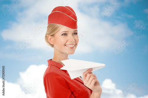 Charming Stewardess Holding Paper Plane In Hand. Sky With Clouds - 72800565