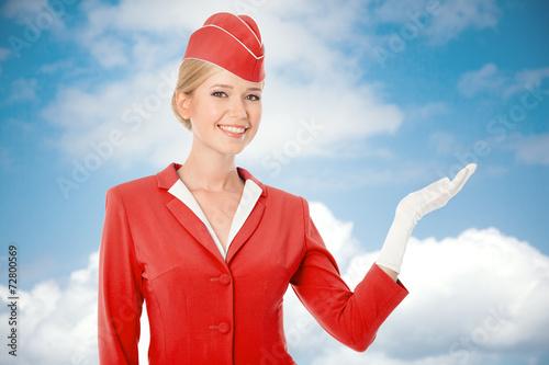 Leinwanddruck Bild Charming Stewardess Dressed In Red Uniform Holding In Hand. Sky