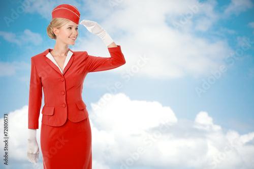 Leinwandbild Motiv Charming Stewardess Dressed In Red Uniform. Sky With Clouds Back
