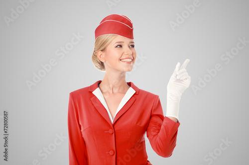 Leinwanddruck Bild Charming Stewardess Dressed In Red Uniform Pointing The Finger O