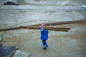 Construction worker carries board