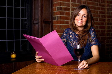 young woman holding a menu in a bar.