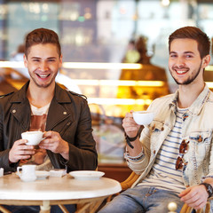 Two young hipster guy sitting in a cafe chatting and drinking
