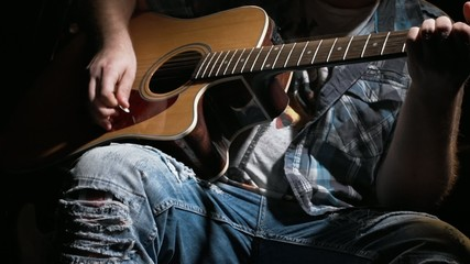 Close up of a guitar and a young man