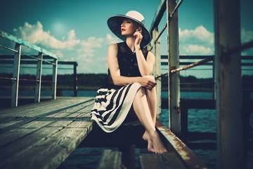 Beautiful stylish woman on old wooden pier
