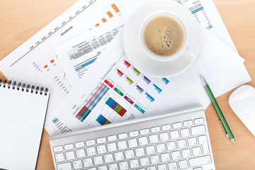 Coffee cup over papers with numbers and charts