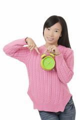 Beautiful Chinese woman holding a green alarm clock