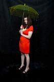 lass wearing red dress stands under an umbrella poster