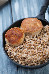 Close-up of a frying pan with buckwheat and meat cutlets