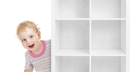 Adorable kid boy behind empty white shelves