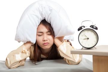 Sleepy Asian girl use pillow cover ears and alarm clock