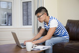 Chinese man at home on sofa using a laptop.