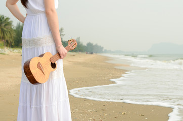 Young Asian girl with ukulele on the beach