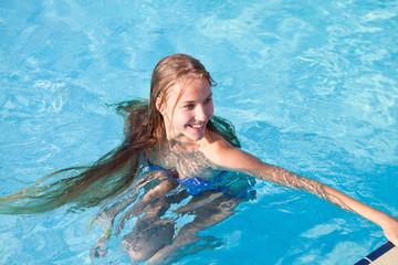 Блондинка с длинными волосами плавает в бассейне
