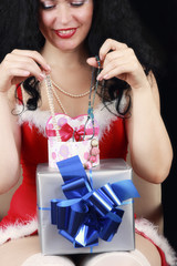 Christmas sensual brunette girl with gifts isolated on black