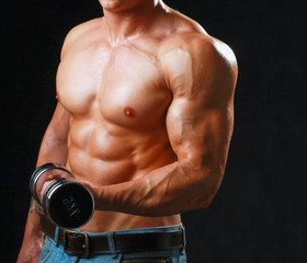 Handsome muscular man working out with dumbbells over black
