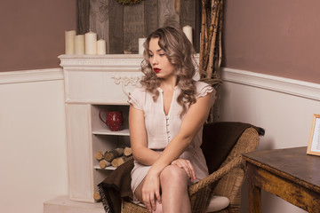 beautiful girl sitting in a chair by the fireplace