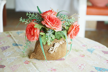 orange artificial roses in small sack in living room