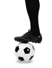 Leg of soccer player with ball on white