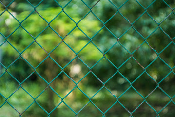 Metal fence with bokeh green background