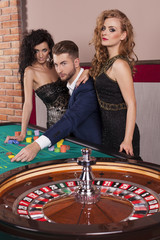 Women and man by roulette table at casino