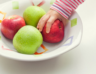 Child taking apple from bowl