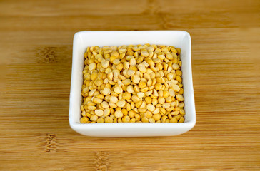 Aerial closeup of yellow split peas in white bowl