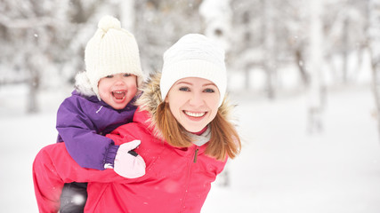 happy family mother and baby girl daughter playing  in winter
