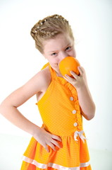 girl eating an orange and licks her fingers