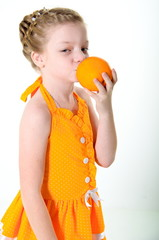 girl eating an orange and licks her fingers