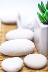 spa, heath and beauty concept - massage stones,towel with flower