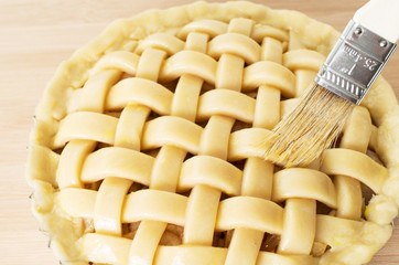 Apple pie in preparation with tip of brush