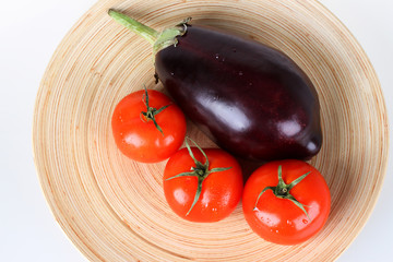 Fresh red tomatoes and aubergine on wooden plate