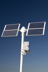 Two solar panels mounted on a post