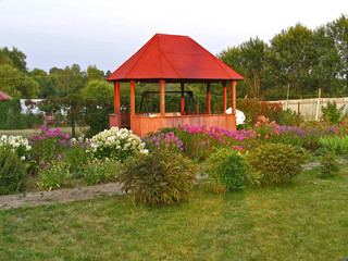 Wooden arbour in floral garden at sunset