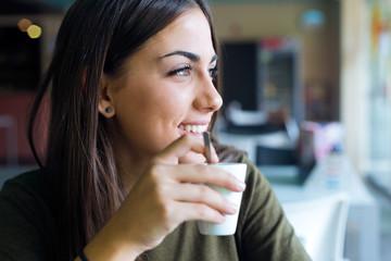 Beautiful girl drinking coffee sitting indoor in urban cafe.