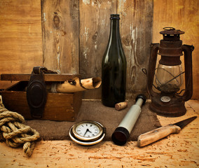 Vintage kerosene lamp, spyglass and a bottle on a wooden grungy