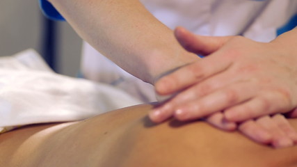 Massage of female back in the masseur.