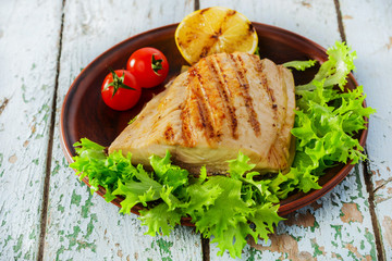 Grilled fish fillet with lemon and cherry tomatoes
