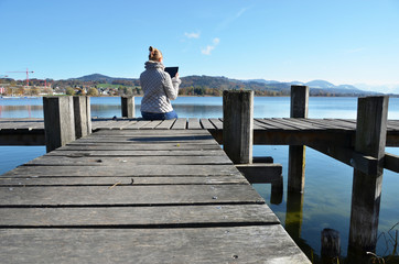 Girl reading from a tablet on the wooden jetty against a lake. S