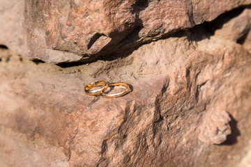 two wedding rings on a stone wall